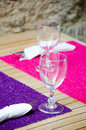 Table serving in street cafe with wine glasses and bright napkins Stock Photo