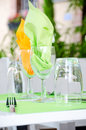 Table serving with wine glasses and bright napkins in street cafe Stock Images