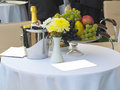 Table set for romantic dinner with champagne flowers and fruits Royalty Free Stock Photo