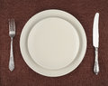 Table setting beige plates vintage fork and knife on a brown linen tablecloth Royalty Free Stock Photo