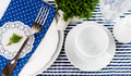 Table setting for breakfast with napkins cups plates in blue on a white background isolated Royalty Free Stock Images