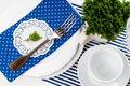 Table setting for breakfast with napkins cups plates in blue on a white background isolated Royalty Free Stock Photo