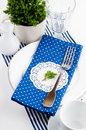 Table setting for breakfast in navy blue tones with napkins cups plates on a white background isolated Royalty Free Stock Photography