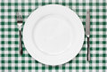 Table setting on green gingham tablecoth place with empty plate knife and fork background popular symbol for diners and cafes Royalty Free Stock Images