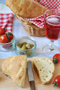 Table setting for italian dinner with fresh bread tomatoes olives red wine ciabatta focaccia Stock Photos