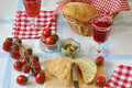 Table setting for italian dinner with fresh bread tomatoes olives red wine ciabatta focaccia Stock Image