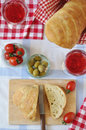 Table setting for italian dinner with fresh bread tomatoes olives red wine ciabatta focaccia Royalty Free Stock Image
