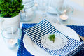 Table setting in navy blue tones for breakfast with napkins cups plates on a white background Stock Photography