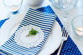 Table setting in navy blue tones for breakfast with napkins cups plates on a white background Royalty Free Stock Photos