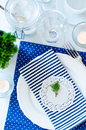 Table setting in navy blue tones for breakfast with napkins cups plates on a white background isolated Royalty Free Stock Photography
