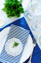 Table setting in navy blue tones for breakfast with napkins cups plates on a white background isolated Stock Image