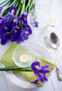 Table setting with purple iris flowers festive vintage cutlery and candles Royalty Free Stock Photos