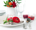 Table setting with red buttercup flowers festive dining candles napkins and shiny new cutlery in white Stock Photos