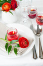 Table setting with red buttercup flowers festive dining candles napkins and shiny new cutlery in white Royalty Free Stock Photography