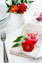 Table setting with red buttercup flowers festive dining candles napkins and shiny new cutlery in white Stock Photography