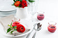 Table setting with red buttercup flowers festive dining candles napkins and shiny new cutlery in white Royalty Free Stock Photos