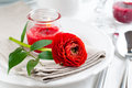 Table setting with red buttercup flowers festive dining candles napkins and shiny new cutlery in white Royalty Free Stock Images