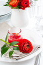 Table setting with red buttercup flowers festive dining candles napkins and shiny new cutlery in white Stock Photo