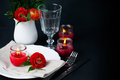 Table setting with red buttercups on a black background Royalty Free Stock Photo