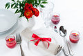 Table setting with red flowers festive dining candles and ribbons in white tones Stock Images