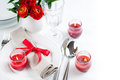 Table setting with red flowers festive dining candles and ribbons in white tones Stock Photos