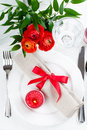 Table setting with red flowers festive dining candles and ribbons in white tones Royalty Free Stock Images