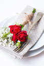 Table setting with red roses, napkins and vintage crockery Royalty Free Stock Photo
