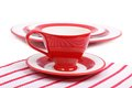 Table setting red tea cup saucer striped napkin isolated white background Royalty Free Stock Image