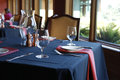 Table setting in a restaurant with a blue tablecloth and red na napkins white plates Stock Images