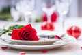 Table setting for valentines or wedding day with red roses. Romantic table setting for two with roses plates cups and cutlery Royalty Free Stock Photo