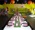 Table settings laid for a party view down long dining of place with pink decorations and dinnerware possibly childs birthday Stock Photo