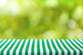 Table top covered with stripped tablecloth on abstract bokeh green background Royalty Free Stock Photo