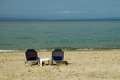 Table for two on beach empty wooden and chairs an empty tropical with a calm sea and the horizon Stock Photography