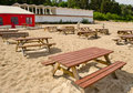 Tables and benches on sea sand and huge cafe tent. Royalty Free Stock Photo