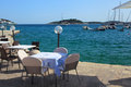 Tables of cafe on the embankment of the city of Hvar. Royalty Free Stock Photo