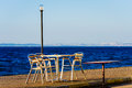 Tables and chairs on the seaside of a local cafe with view of blue sea sky islands in horizon Stock Photo