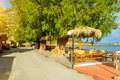 Tables with umbrellas in cafe. Bali, Crete, Greece Royalty Free Stock Photo