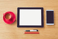 Tablet with blank screen on wooden table office desk mock up view from above and smart phone Stock Photography