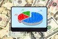Tablet with chart digital pie on background of dollars Royalty Free Stock Image