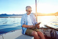 Tablet computer on boat sailing man reading with modern technology and carefree retired senior successful lifestyle Royalty Free Stock Image