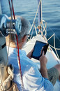 Tablet computer on boat sailing man reading with modern technology and carefree retired senior successful lifestyle Stock Image