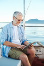 Tablet computer on boat sailing man reading with modern technology and carefree retired senior successful lifestyle Stock Photos