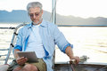 Tablet computer on boat sailing man reading with modern technology and carefree retired senior successful lifestyle Stock Photo