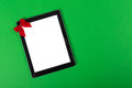 Tablet computer with a bow on green background closeup of small red in the corner copy space available the and Royalty Free Stock Photography