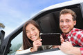 Tablet computer couple in car showing screen driving with app or message young happy drivers on road trip asian woman caucasian Stock Images