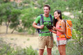 Tablet computer couple hiking using internet app and pc guide book on hike in zion national park interracial Royalty Free Stock Image