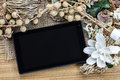 Tablet computer tablet pc and dry flowers frame on wooden background with Royalty Free Stock Photo