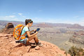 Tablet computer woman hiking in grand canyon using travel app or map during her hike multiethnic hiker girl relaxing on south Royalty Free Stock Photos