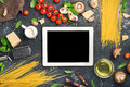 Tablet with copy space with ingredients for cooking Italian past Royalty Free Stock Photo