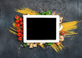 Tablet with copy space and ingredients for cooking Italian pasta Royalty Free Stock Photo